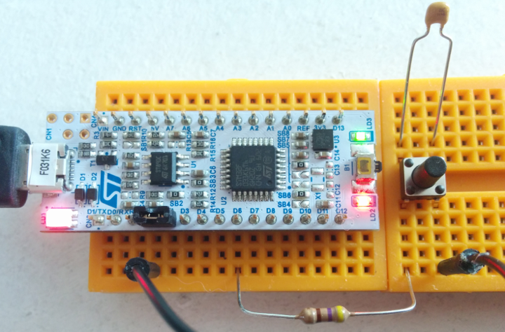 Nucleo board on a breadboard with a button.